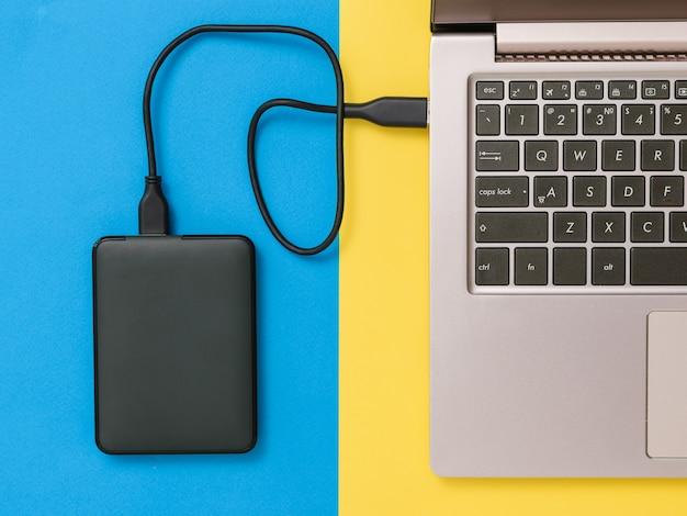 Schwarze festplatte und laptop auf gelbem und blauem hintergrund. der blick von oben. das konzept des backup-speichers. flach liegen.
