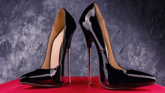 Schwarze fetisch glänzende lackleder stiletto high heels mit knöchelriemen