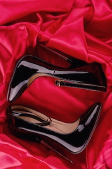 Schwarze fetisch glänzende lackleder-stöckelschuhe mit knöchelriemen auf rotem satinhintergrund