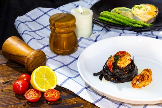 Schwarze fettuccine-spaghetti mit garnelen, tintenfisch mit petersilie lachssteak an