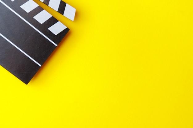Schwarze filmklappe des kinos auf gelbem hintergrund. moderne kinematographie, filmemachen.