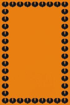 Schwarze fledermäuse auf einem orangefarbenen hintergrund halloween-rahmen-design-ressource