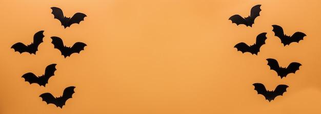 Schwarze fledermäuse auf orange hintergrund