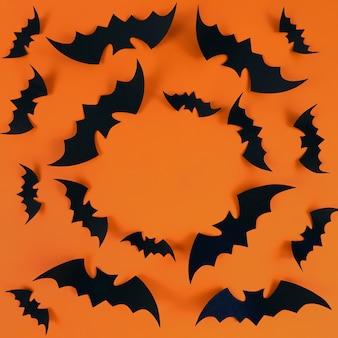 Schwarze fledermäuse auf orangem hintergrund mit textfreiraum