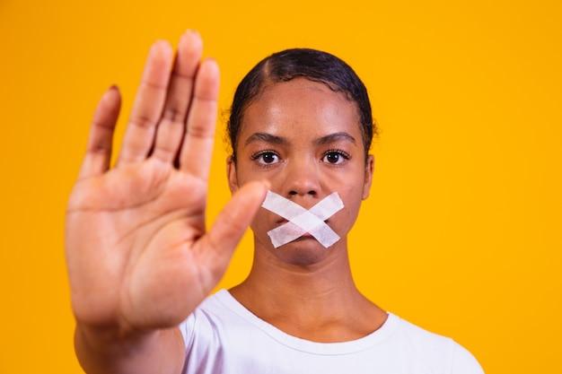 Schwarze frau auf gelbem hintergrund mit schweigendem mund. konzept von vorurteilen, missbrauch und rassismus