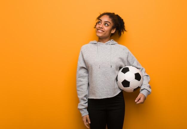 Schwarze frau der jungen eignung, die vom erreichen von zielen und von zwecken träumt. einen fußball halten.