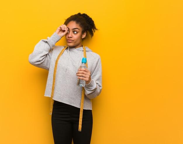 Schwarze frau der jungen eignung, welche die geste eines fernglases macht halten einer wasserflasche.