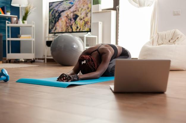 Schwarze frau, die auf yoga-kamerad sitzt und entspannenden körper ausdehnt