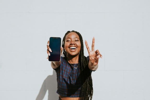 Schwarze frau, die ein av-zeichen mit einem leeren telefon zeigt