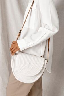 Schwarze frau, die eine weiße gewebte baumwollseiltasche trägt