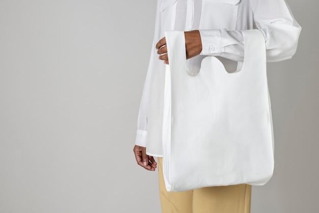 Schwarze frau, die eine weiße wiederverwendbare einkaufstüte trägt