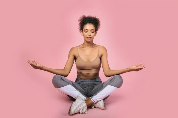 Schwarze frau, die im yoga acana auf rosa hintergrund sitzt. gesundes lebensstilkonzept. copispace.