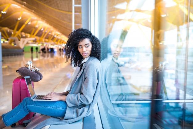 Schwarze frau, die mit laptop am flughafen wartet am fenster arbeitet