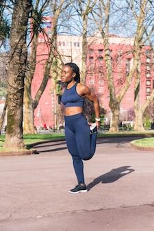 Schwarze frau, die sich aufwärmt und die muskeln dehnt, um ein körperliches training zu beginnen oder in einem öffentlichen straßenpark zu joggen?