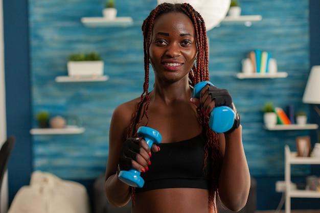 Schwarze frau, die sich um die körperarbeit kümmert und die armmuskulatur mit hanteln während des trainings trainiert. positiver, fröhlicher, sportlicher, starker athlet im wohnzimmer.