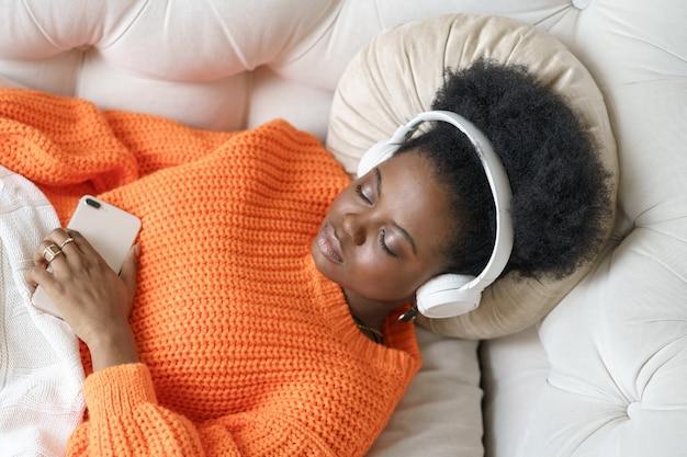 Schwarze frau im orangefarbenen pullover, der drahtlose kopfhörer trägt, musik hört, sich ausruht, auf couch liegend