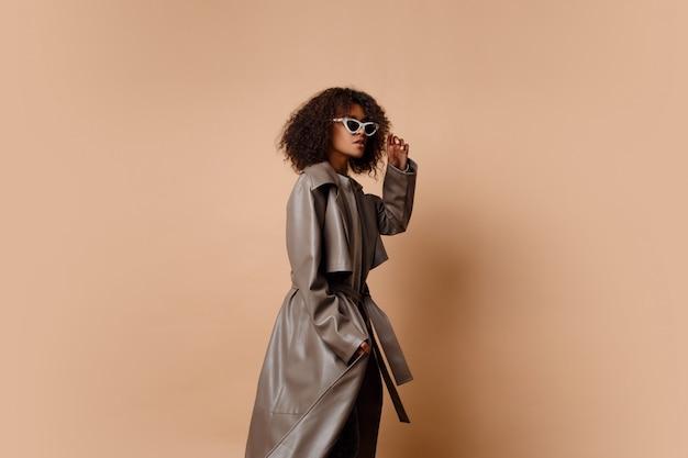 Schwarze frau in der trendigen grauen lederjacke, die über beigem hintergrund im studio aufwirft. winter- und herbstmode-look.