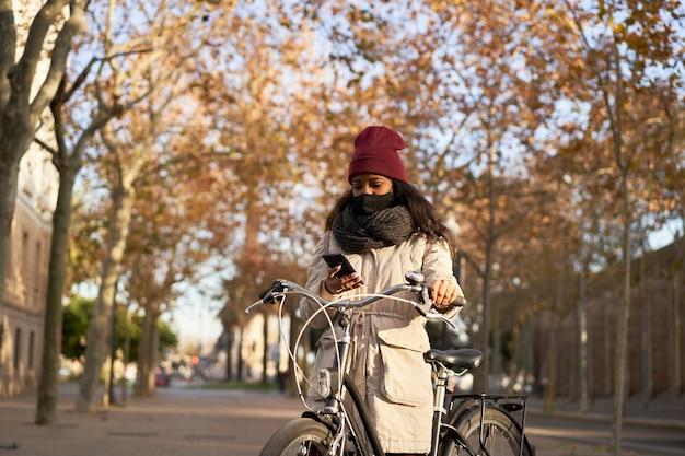 Schwarze frau in der winterkleidung, die mit einem fahrrad steht, das am telefon in einer stadt bei sonnenuntergang spricht.