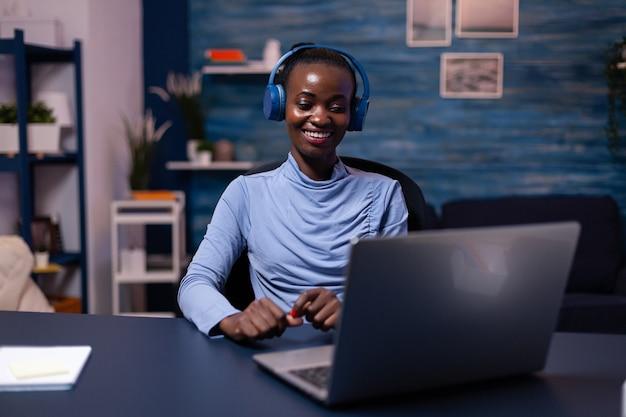 Schwarze frau in guter laune mit kopfhörer, die musik hört, die an der frist aus dem homeoffice arbeitet. am schreibtisch sitzen. afrikanischer freiberufler, der spät ein neues projekt erstellt.