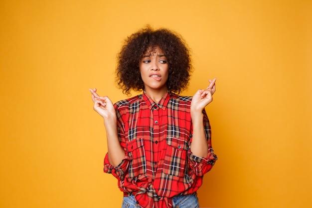 Schwarze frau kreuzt die finger, hofft, dass alle wünsche über leuchtend orange hintergrund wahr werden. menschen, körpersprache und glück.