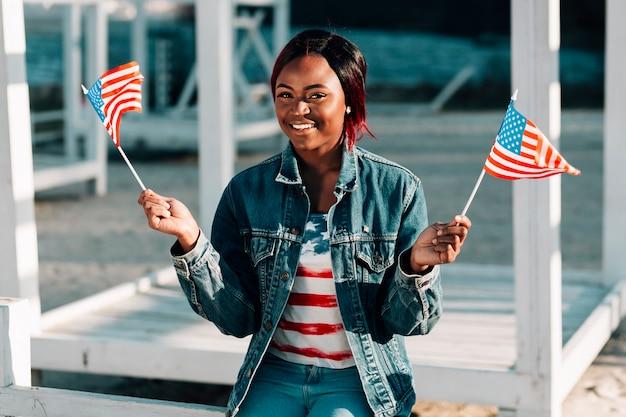 Schwarze frau mit amerikanischen flaggen am strand sitzen