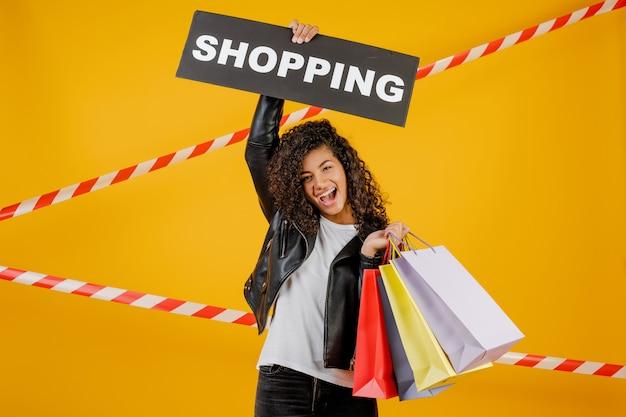Schwarze frau mit dem einkaufszeichen und bunten einkaufstaschen lokalisiert über gelb mit signalband