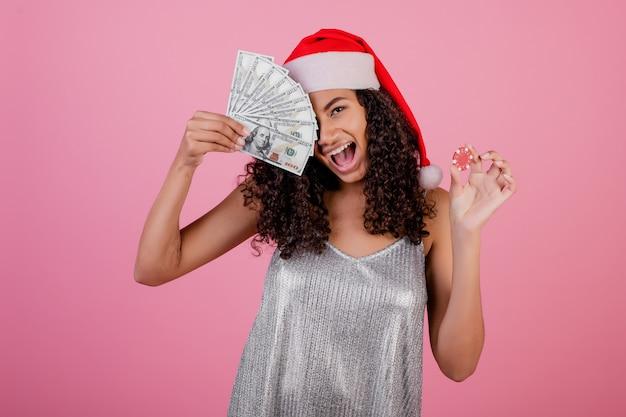 Schwarze frau mit dem kasinopokerchip und bargeld, die feiertag sankt-hut über rosa tragen