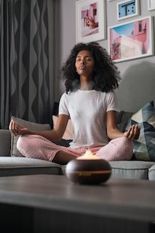 Schwarze frau mit dem lockigen haar, das auf sofa in lotushaltung sitzt und meditiert