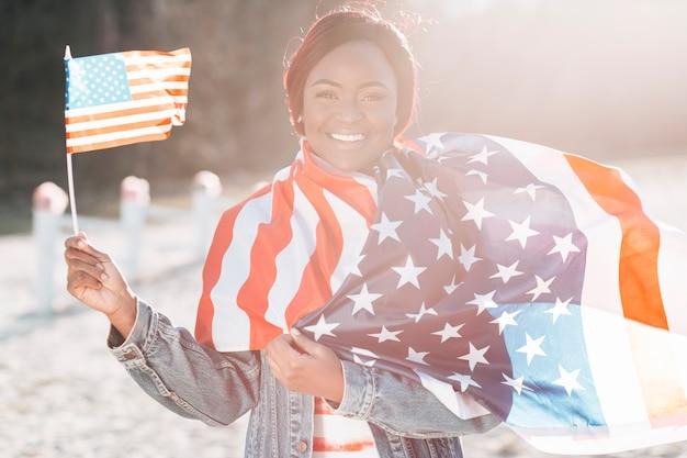 Schwarze frau mit den amerikanischen flaggen, die auf sand stehen