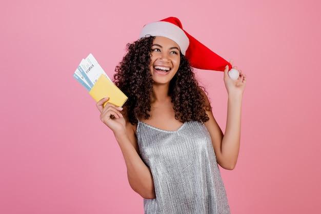 Schwarze frau mit den flugtickets und pass, die den weihnachtshut lokalisiert über rosa tragen