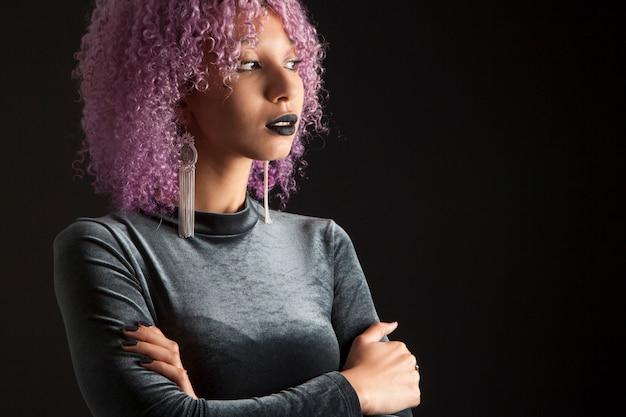 Schwarze frau mit einem bunten lila afro-haar in schwarz gekleidet
