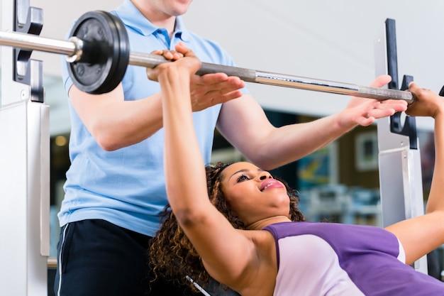 Schwarze frau mit trainer, der gewichte im fitnessstudio für fitness hebt