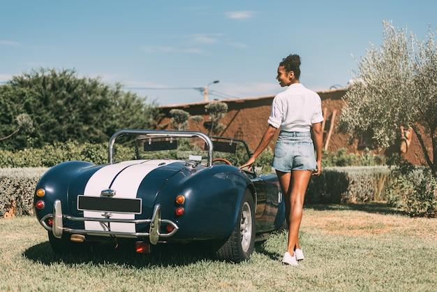 Schwarze frau und oldtimer cabrio