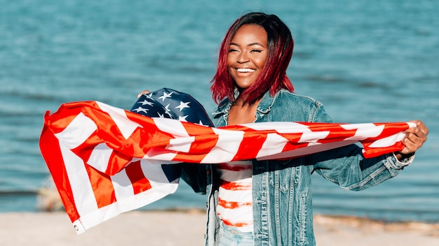 Schwarze frau, welche die amerikanische flagge wellenartig bewegt in wind hält