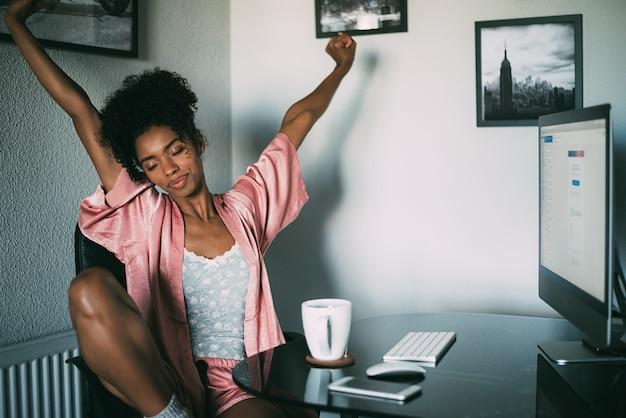 Schwarze frau zu hause, die morgens mit computer und kaffee ausdehnt