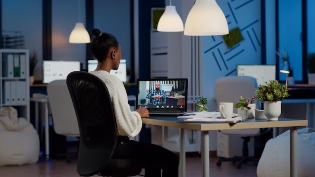 Schwarze freiberuflerin diskutiert mit gelähmtem kunden über videoanruf um mitternacht aus dem geschäftsbüro mit kopfhörer. geschäftsfrau mit virtueller konferenz, die während des online-meetings vor der webcam spricht