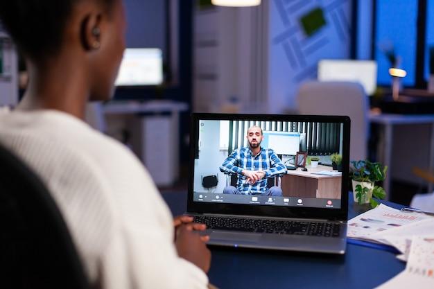 Schwarze freiberuflerin diskutiert mit gelähmtem kunden über videoanruf um mitternacht aus dem geschäftsbüro mit kopfhörer head