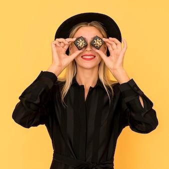 Schwarze freitag-einkaufsfrau, die ihr gesicht mit geschenkboxen bedeckt