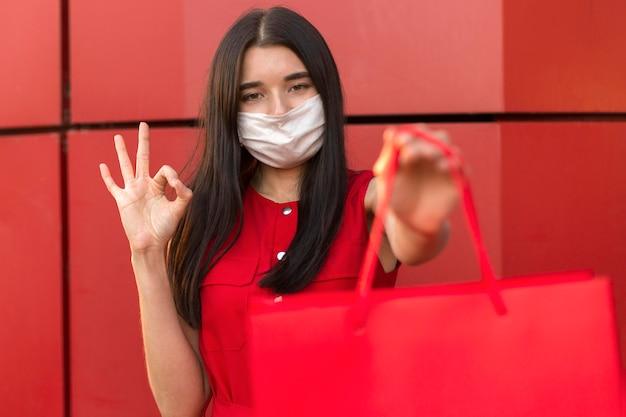 Schwarze freitag-verkäuferin, die maske ok zeichen trägt