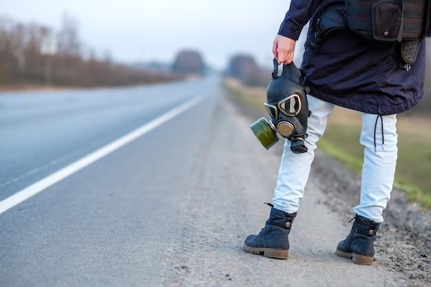 Schwarze gasmaske in der hand eines mädchens, das am rand einer landstraße steht