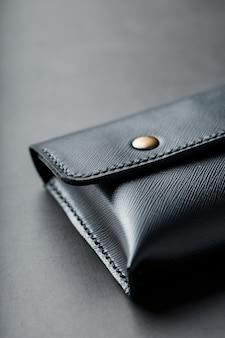 Schwarze geldbörse aus echtem leder auf dunklem