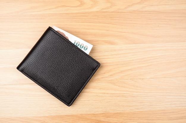 Schwarze geldbörse mit geld auf braunem hölzernem tabellenhintergrund