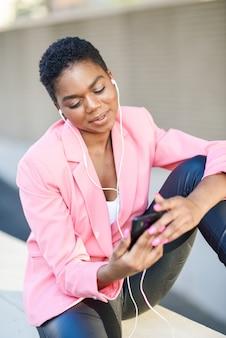 Schwarze geschäftsfrau, die draußen sitzt, sprechend über videokonferenz mit ihrem intelligenten telefon.