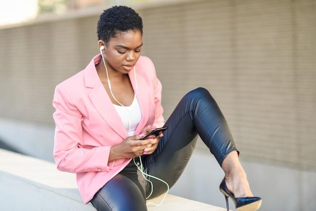 Schwarze geschäftsfrau, die draußen unter verwendung des smartphone mit kopfhörern sitzt