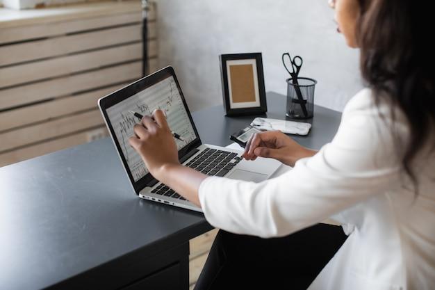 Schwarze geschäftsfrau, die laptop für die analyse von daten börsen forex-handelsdiagramm börsenhandel online-finanzinvestitionskonzept nahaufnahme verwendet