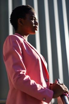 Schwarze geschäftsfrau, die nahes geschäftslokalgebäude steht