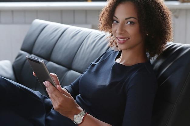 Schwarze geschäftsfrau im strengen schwarzen kleid, die ihre e-mails am tablett überprüft