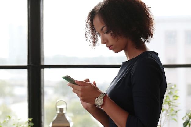 Schwarze geschäftsfrau im strengen schwarzen kleid, die ihre e-mails am telefon überprüft