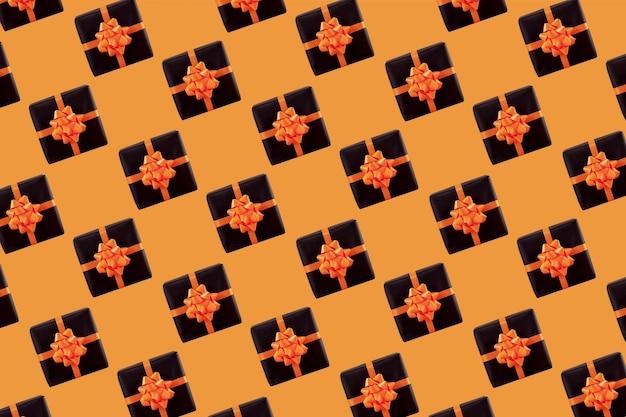 Schwarze geschenkbox auf orangem hintergrund. halloween-konzept, kreatives design. muster.