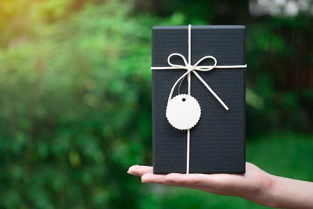 Schwarze geschenkbox der schönheit mit weißem bogen an hand, zum des speziellen geschenks zu geben